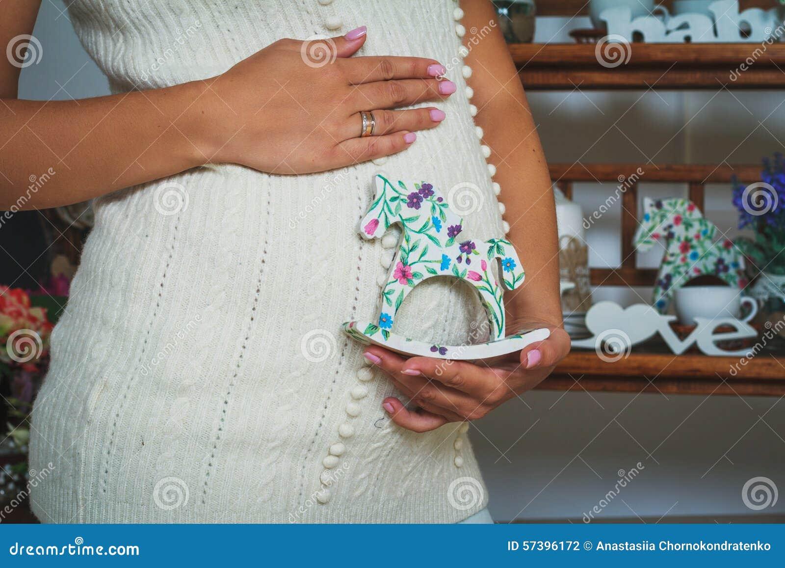 Het zwangere paard-speelgoed van de vrouwenholding dichtbij haar buik