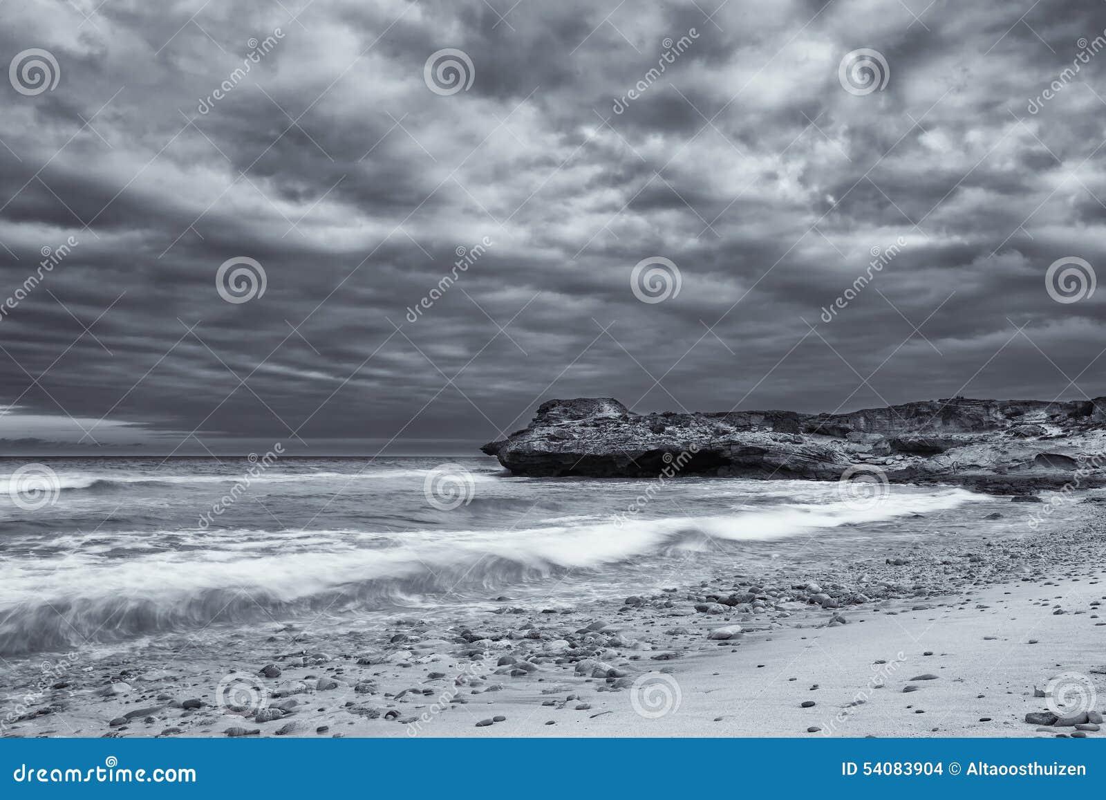 Het zwart-witte landschap van oceaanrotsen en artistieke de wolken bedriegen