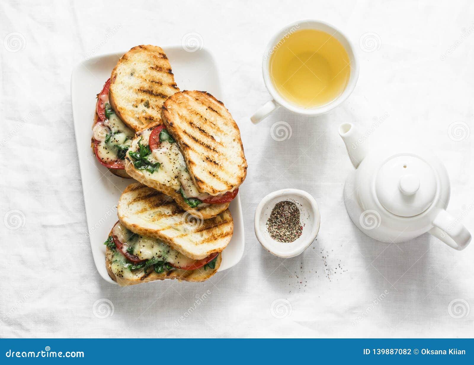 Hete geroosterde tomaten, spinazie, mozarellasandwiches en groene thee - gezond ontbijt, snack op een lichte achtergrond