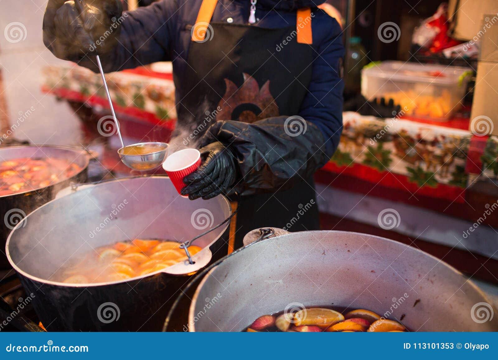 Hete gluhwein of overwogen wijn in een ketel bij eerlijke, lokale traktatie, warm en kruidig Een hete gezonde traditionele citrus