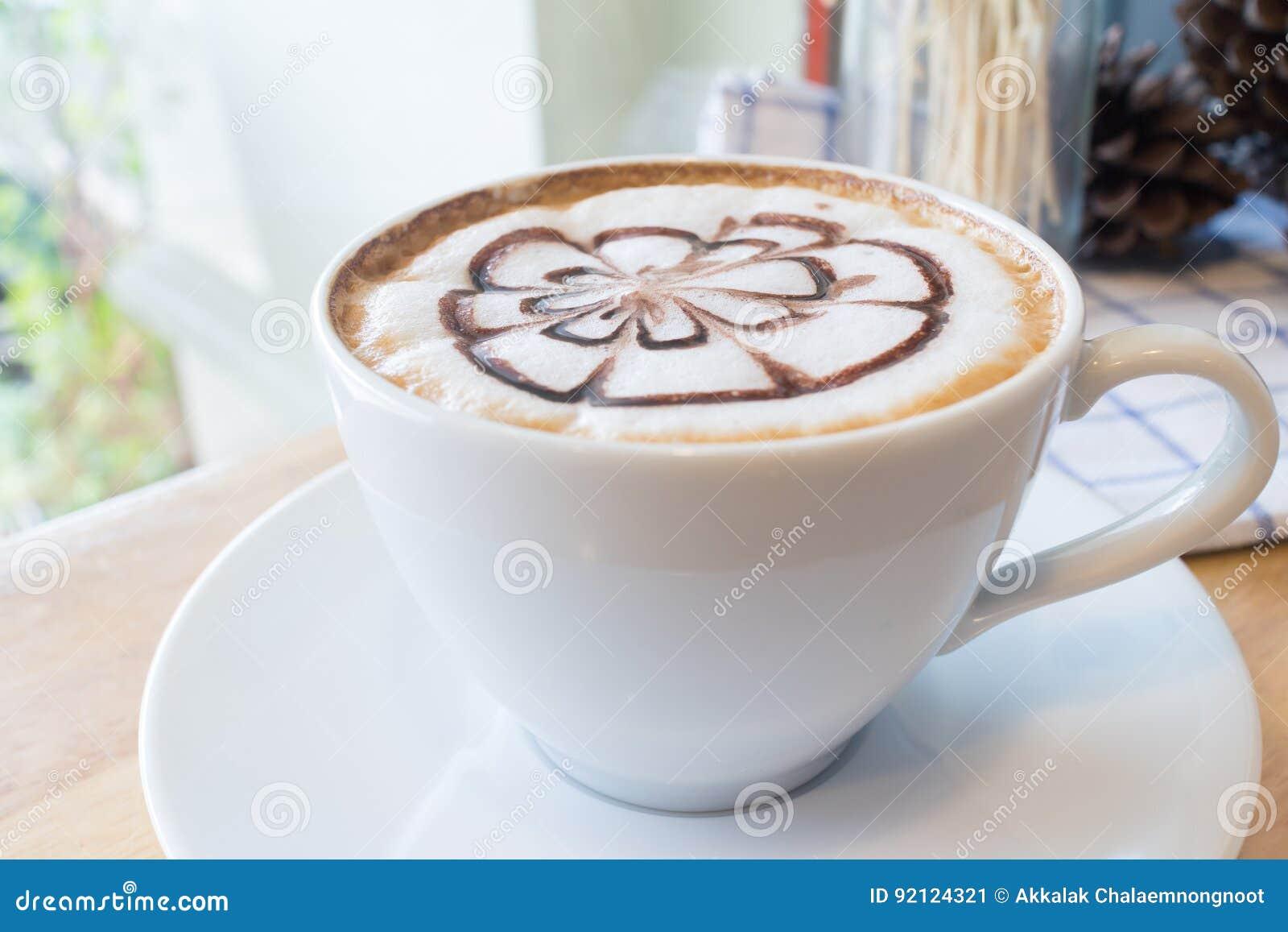 Hete koffie met de kunst van de schuimmelk op het houten bureau