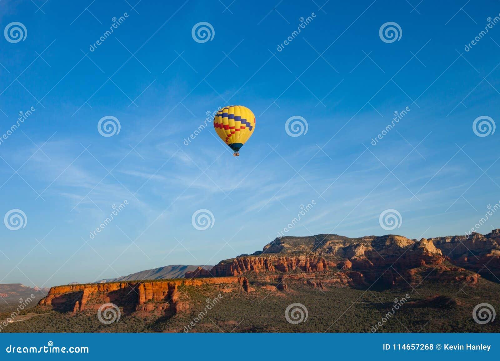 Hete lucht het ballooning over sedona Arizona die ballon en butte tonen