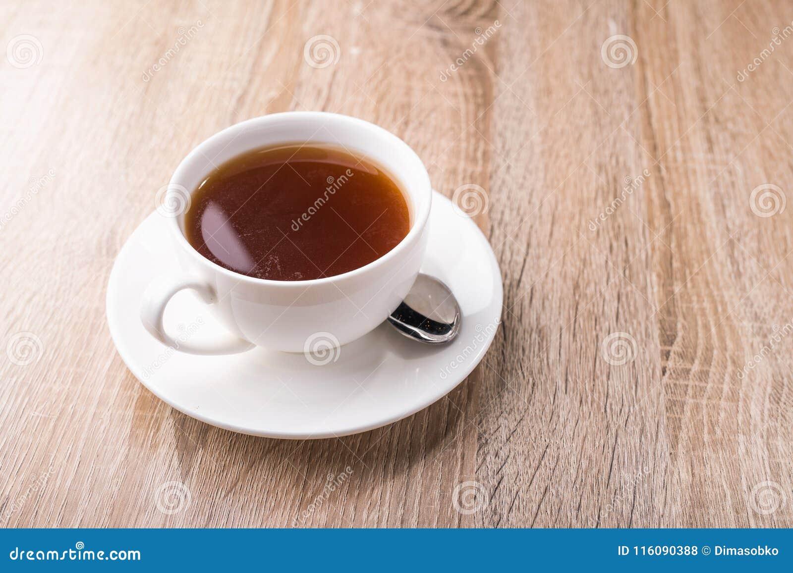 Hete theekop met lepel