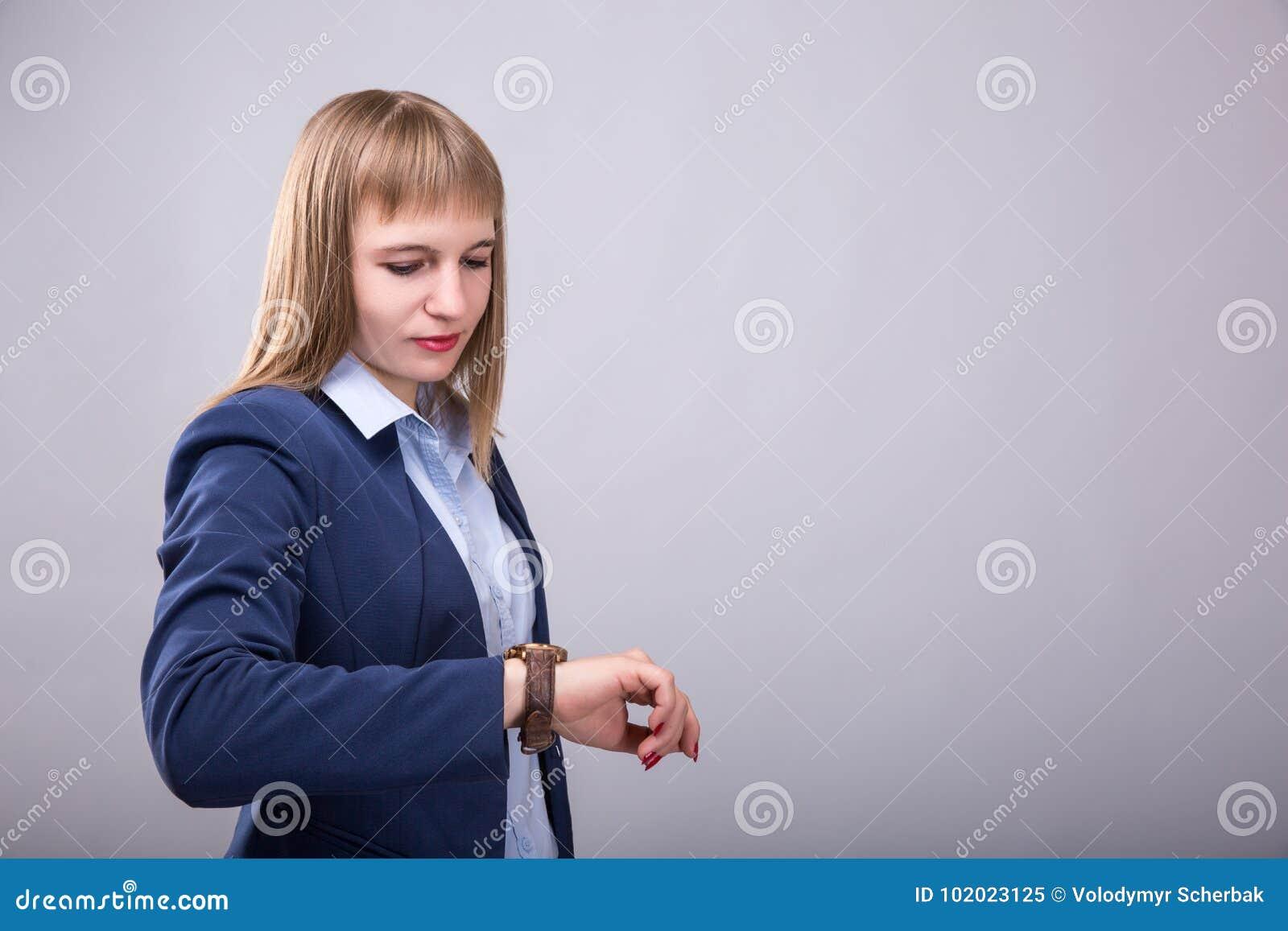 Heure de faire des affaires Jeune femme réfléchie dans la tenue de détente futée vérifiant le temps Regard modèle à la montre