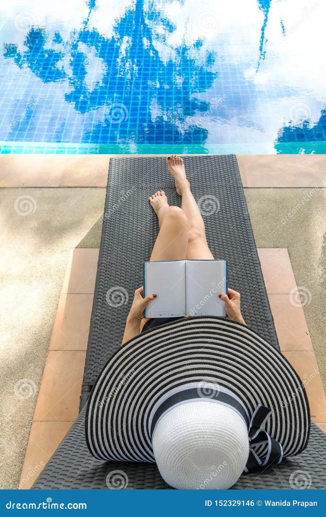 Heure et vacances d ?t? Livre de détente et de lecture de mode de vie de femmes dans le bain de soleil de luxe de piscine, jour d