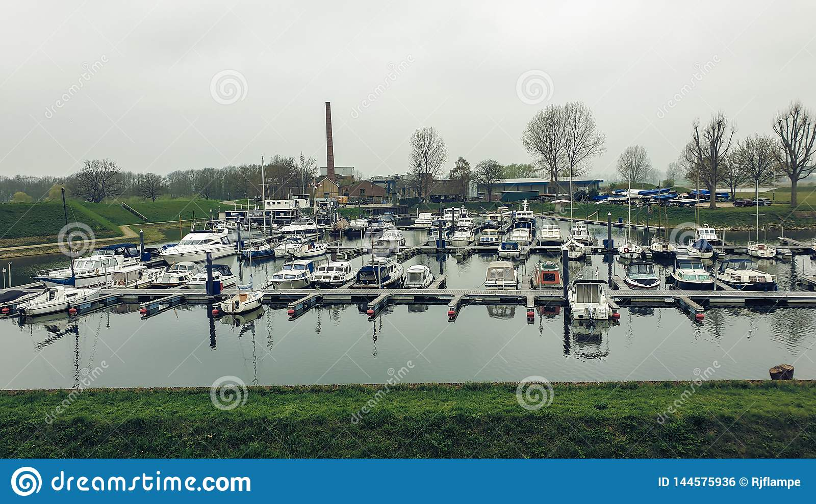 Heusden, Netherlands - 6 April 2019: Boats docked in the harbor, waiting for a nice day