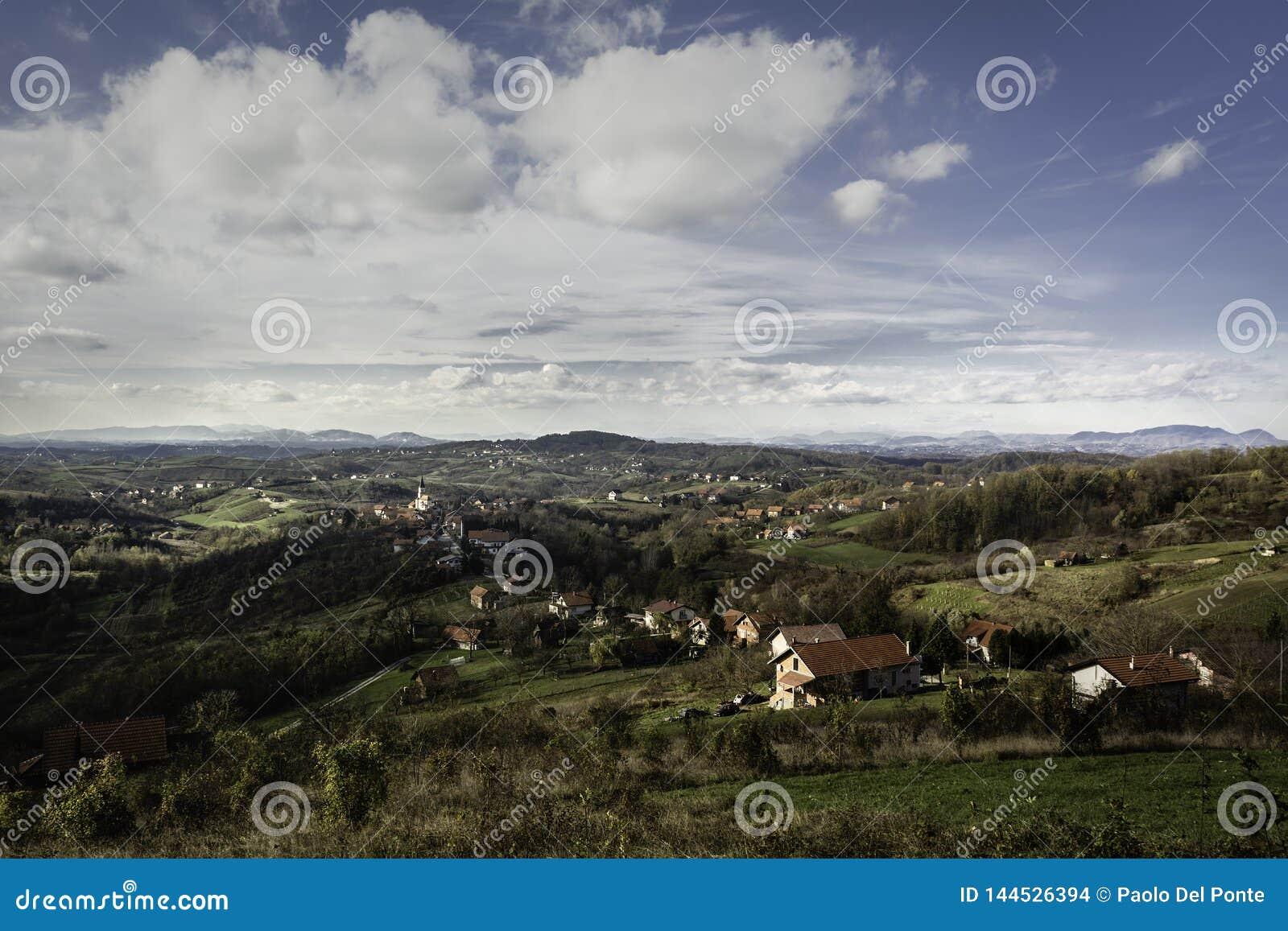 Heuvelig gebied van Zagorje in de vroege herfst met partij van dorpen en bergen in afstand
