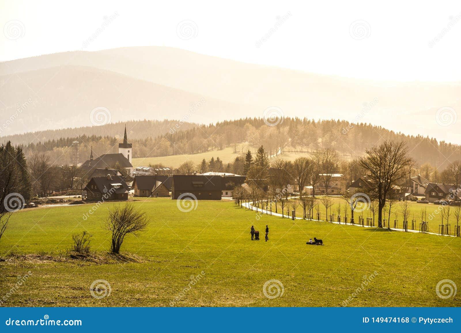 Heuvelig landschap van Jizera-Bergen rond Prichovice-dorp Groene weiden met boomsteeg en kleine landelijke kerk