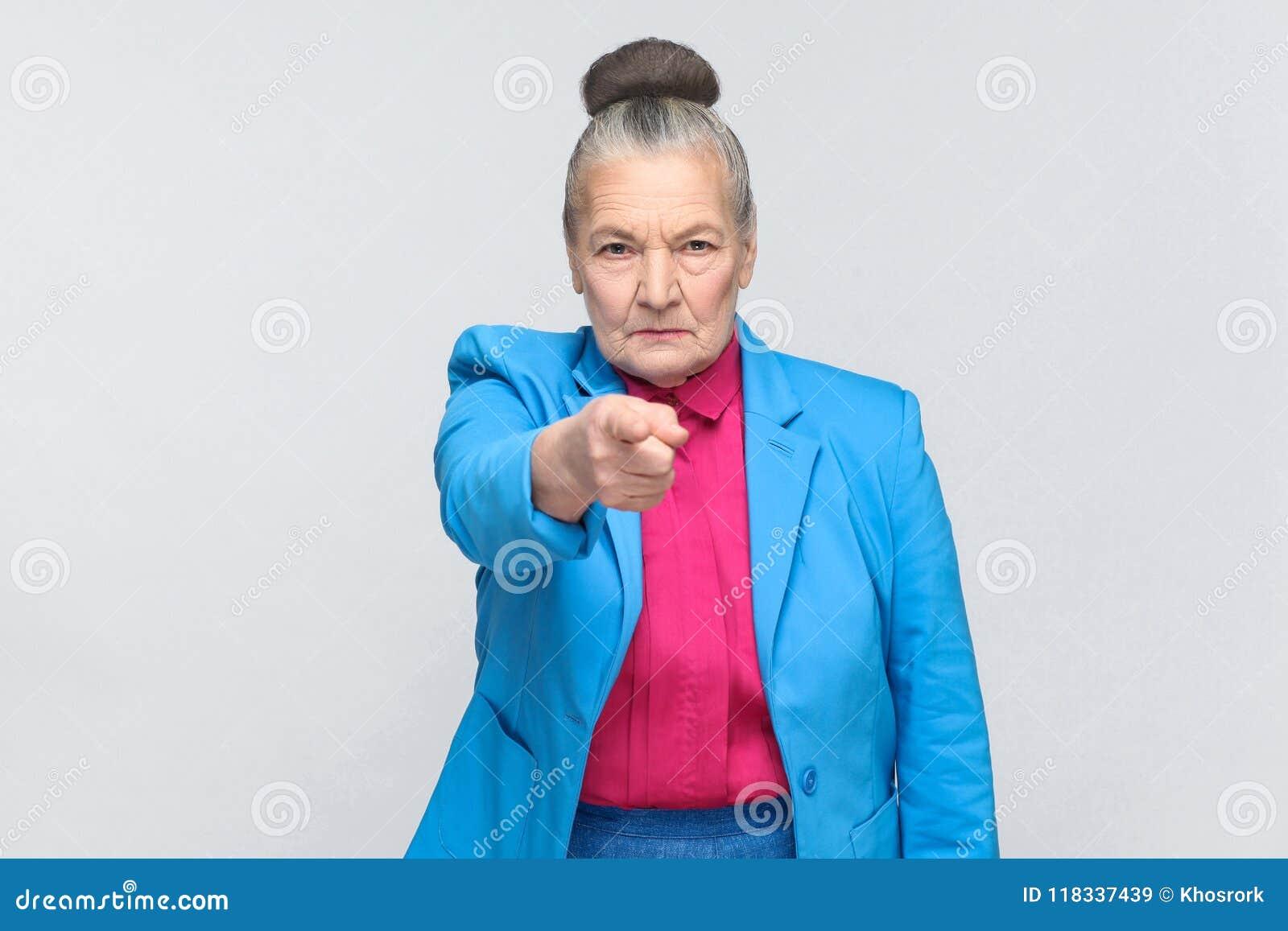 Hey você! Mulher que aponta no dedo da câmera com cara séria