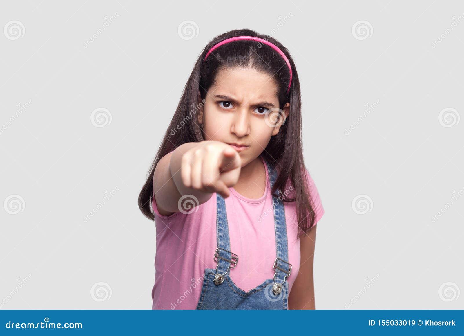 Hey você! Retrato da moça moreno séria no estilo ocasional, no t-shirt cor-de-rosa e na posição azul dos macacões da sarja de Nim