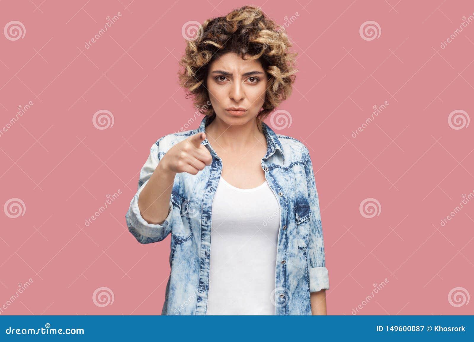 Hey voc? Retrato da jovem mulher s?ria com penteado encaracolado na camisa azul ocasional que est?, olhando e apontando na c?mera