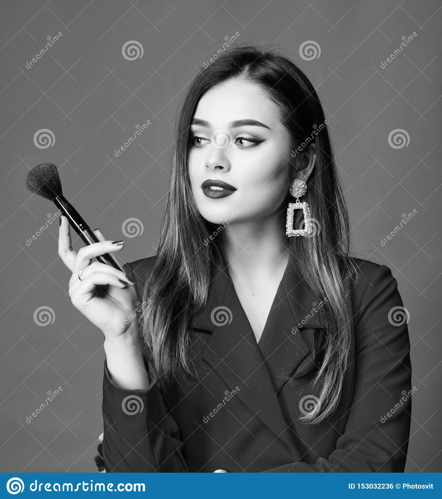 Hiding all imperfections. Attractive woman applying makeup brush. Perfect skin tone. Makeup artist concept. Looking good