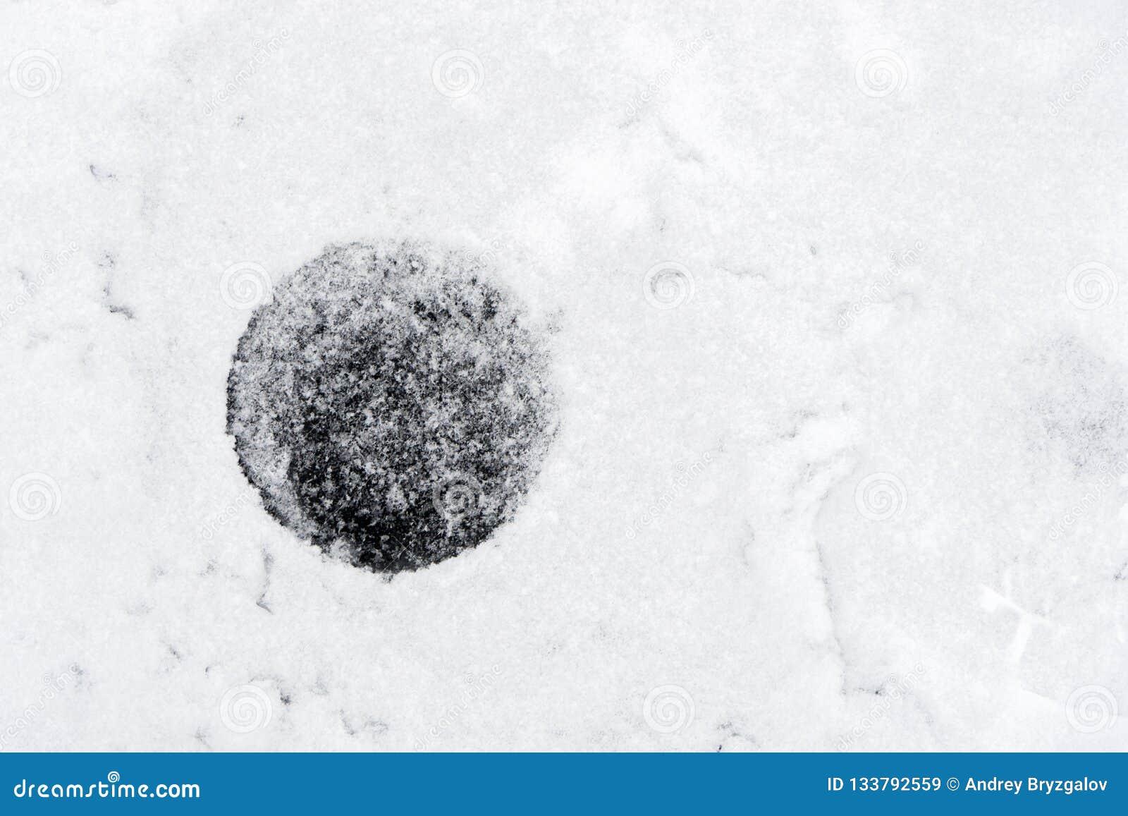 Hielo-agujero del primer en hielo en la charca agujero congelado para la pesca del invierno