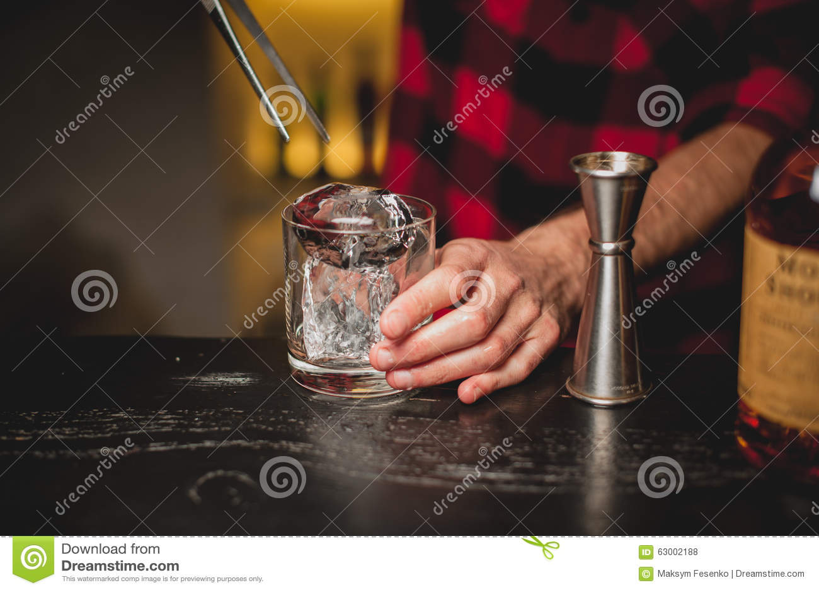 Hielo de colada del camarero en vidrio Camarero que prepara la bebida del cóctel