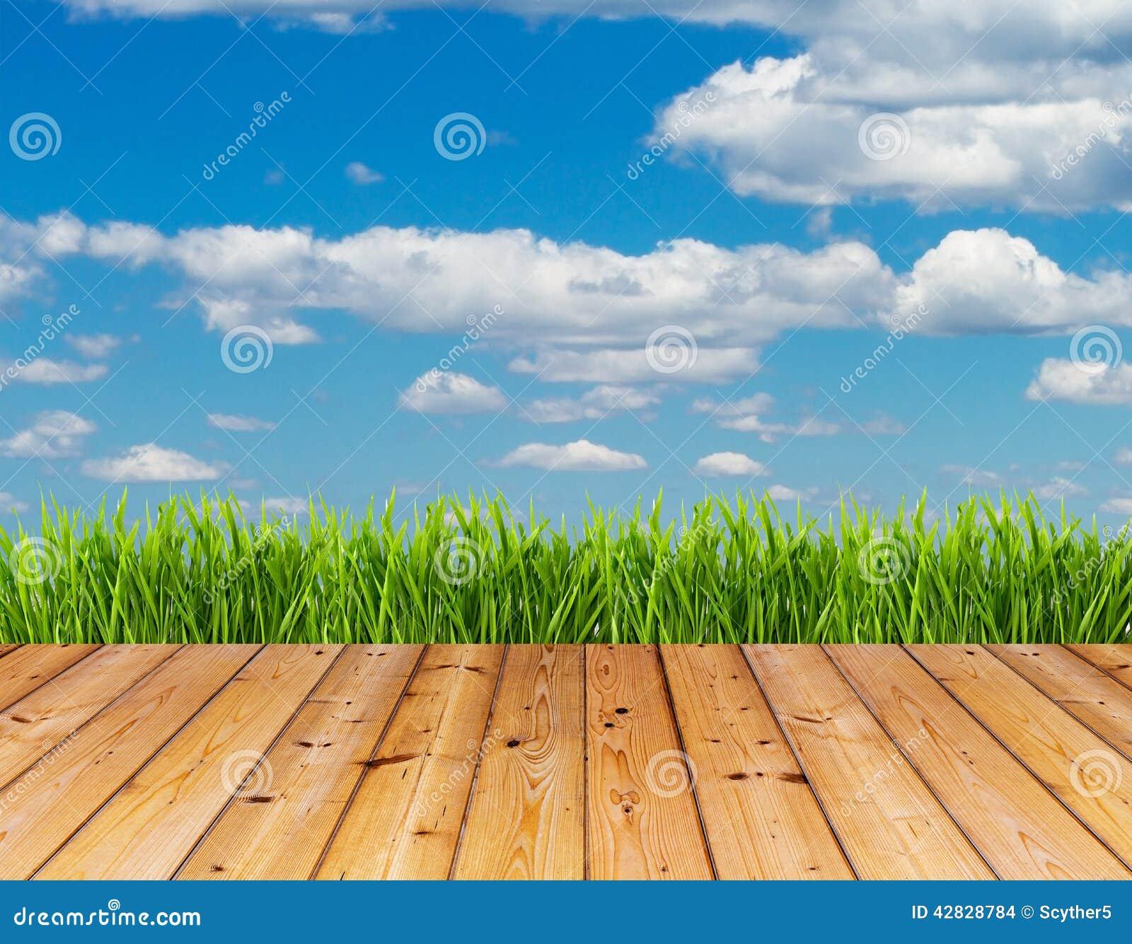 Hierba verde y cielo azul en el fondo de madera del piso