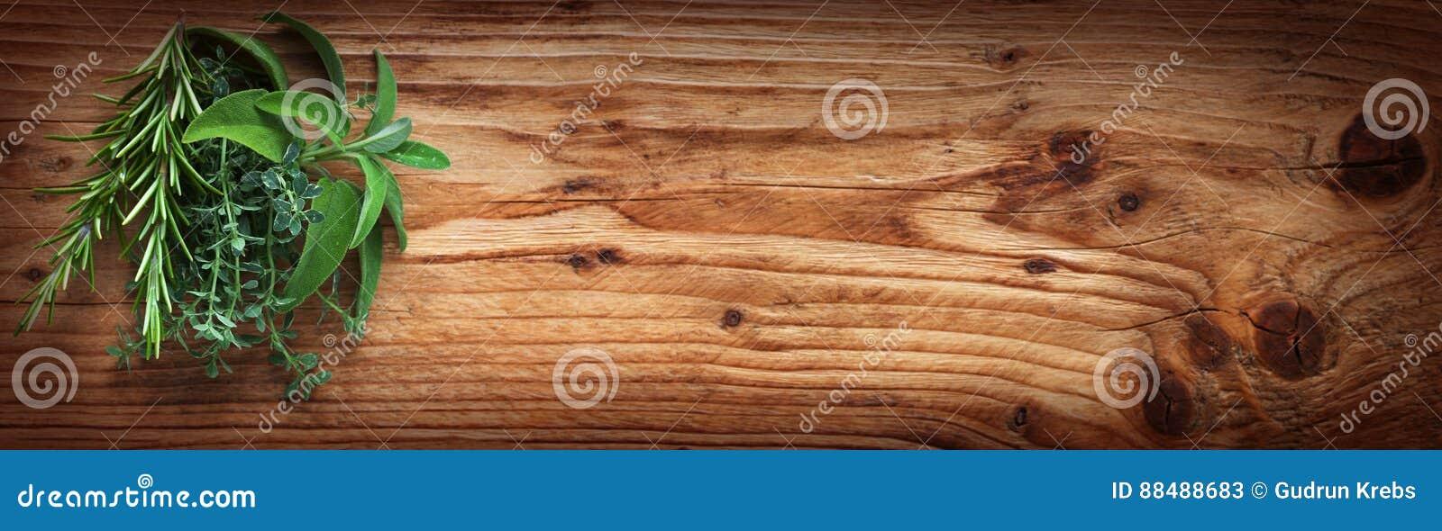 Hierbas frescas de la especia en la madera rústica
