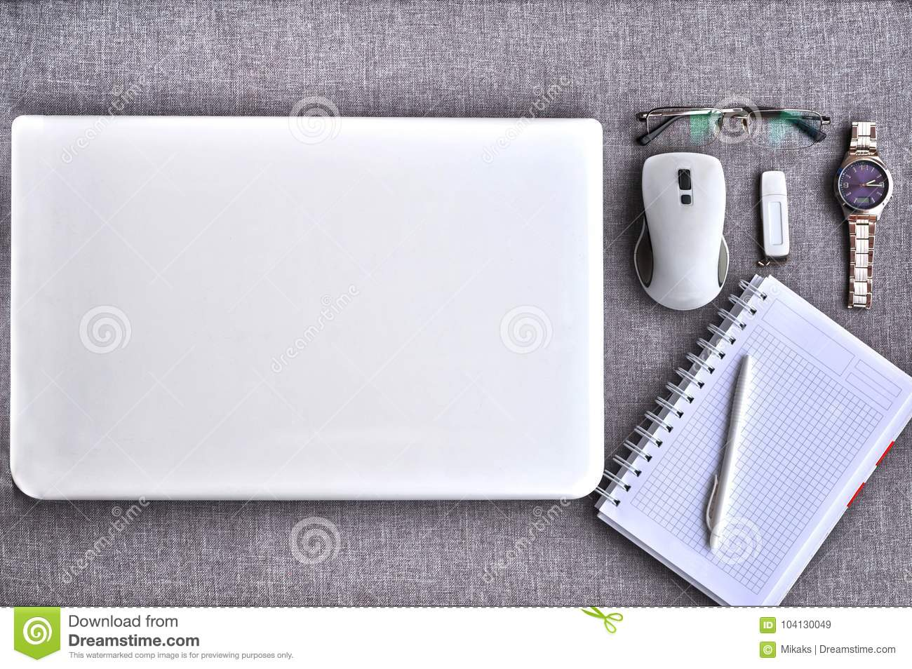 High above view of office workplace with laptop and mouse with paper, pen ,eyeglasses, usb stick, watch on grey desk