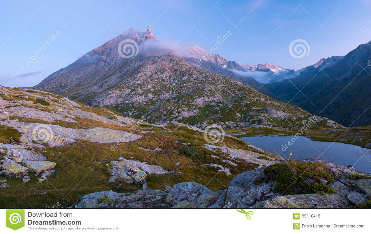 High altitude alpine lake in idyllic land with majestic rocky mountain peaks. Long exposure at dusk. Wide angle view on the Alps.