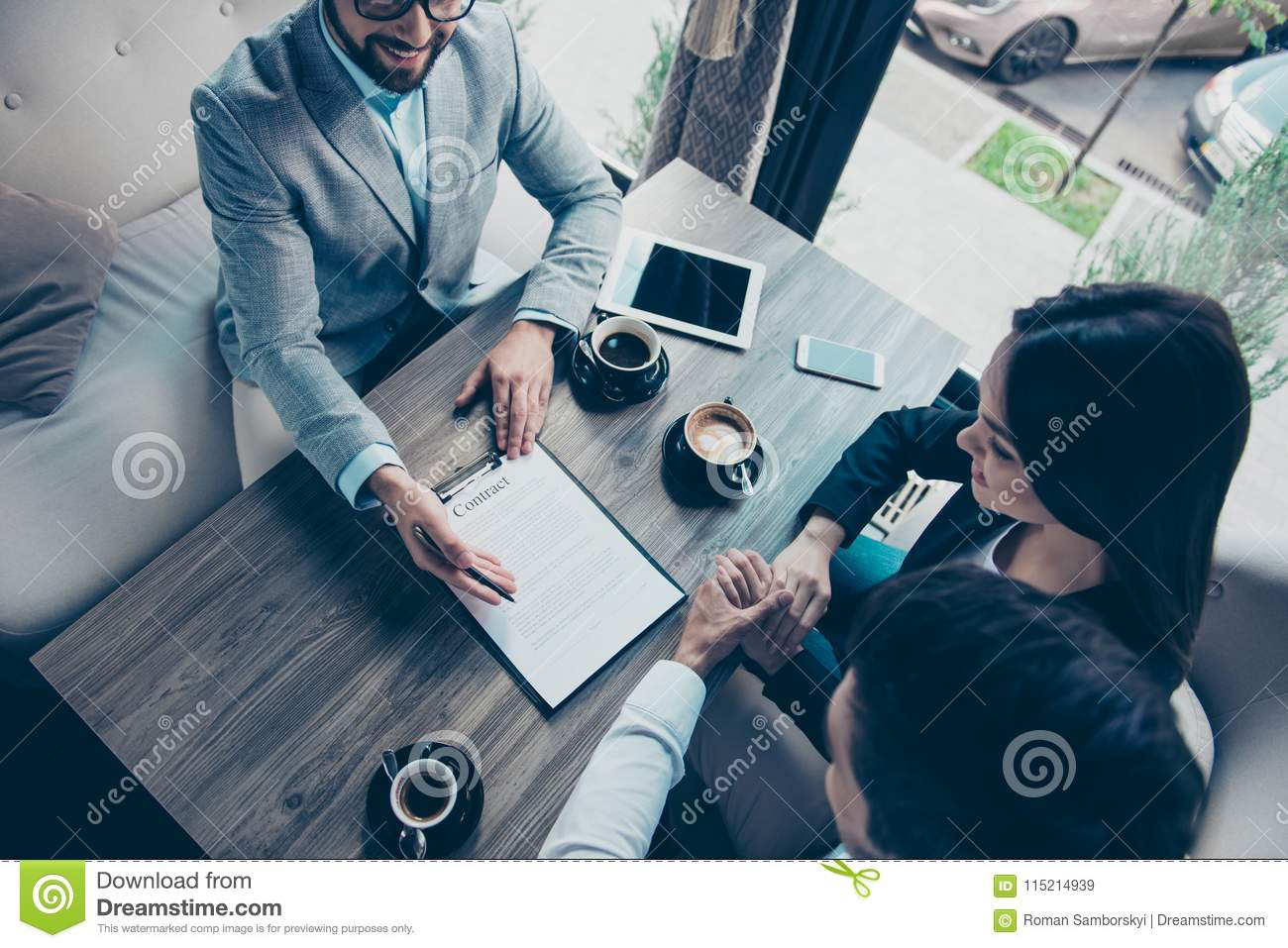 High angle cropped photo of family making a deal with lawyer about their business in cafe with cups of coffee. Men is going to si