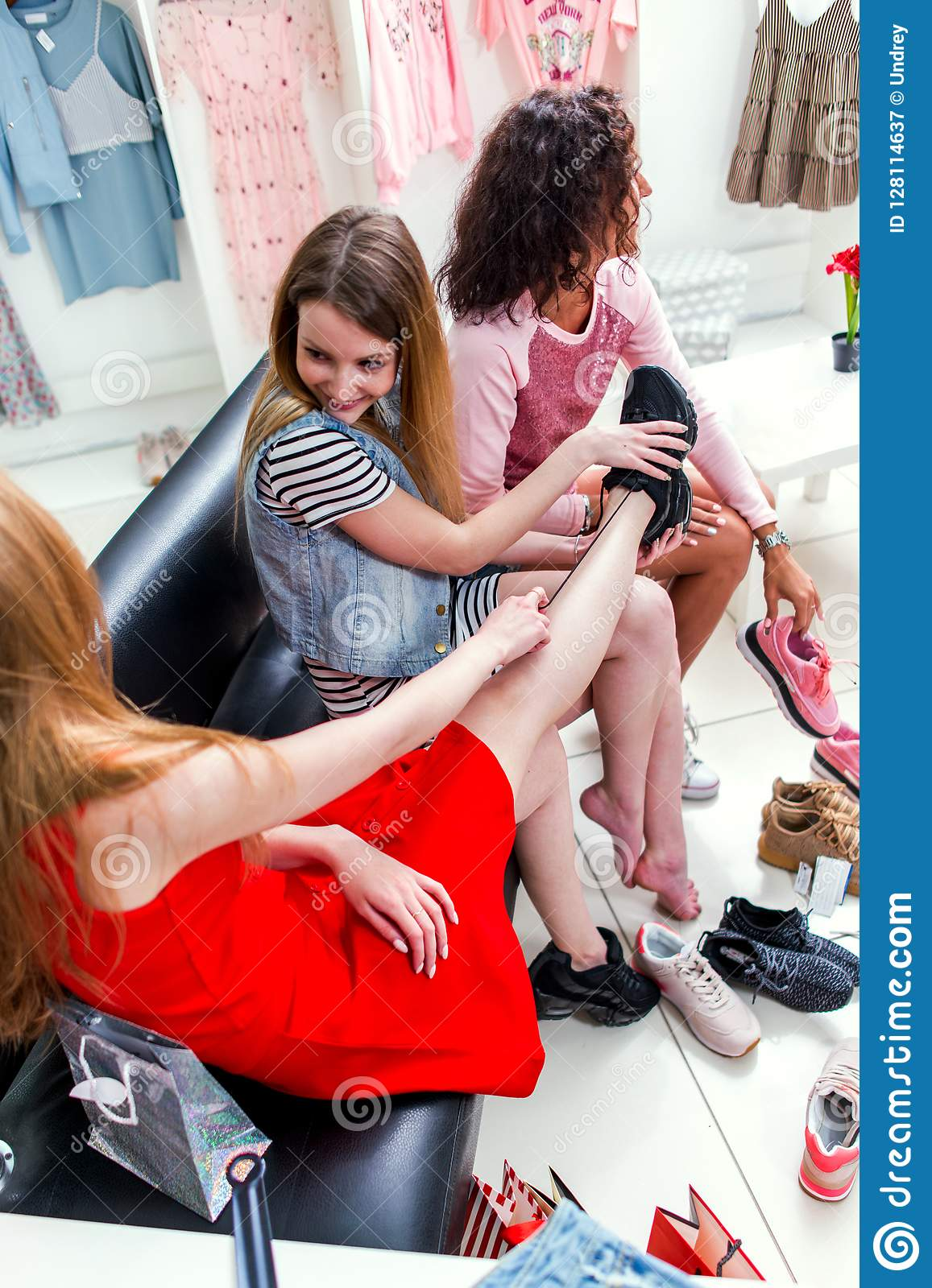 High-angle shot of smiling girlfriends choosing putting on sports shoes sitting on bench chatting and laughing while