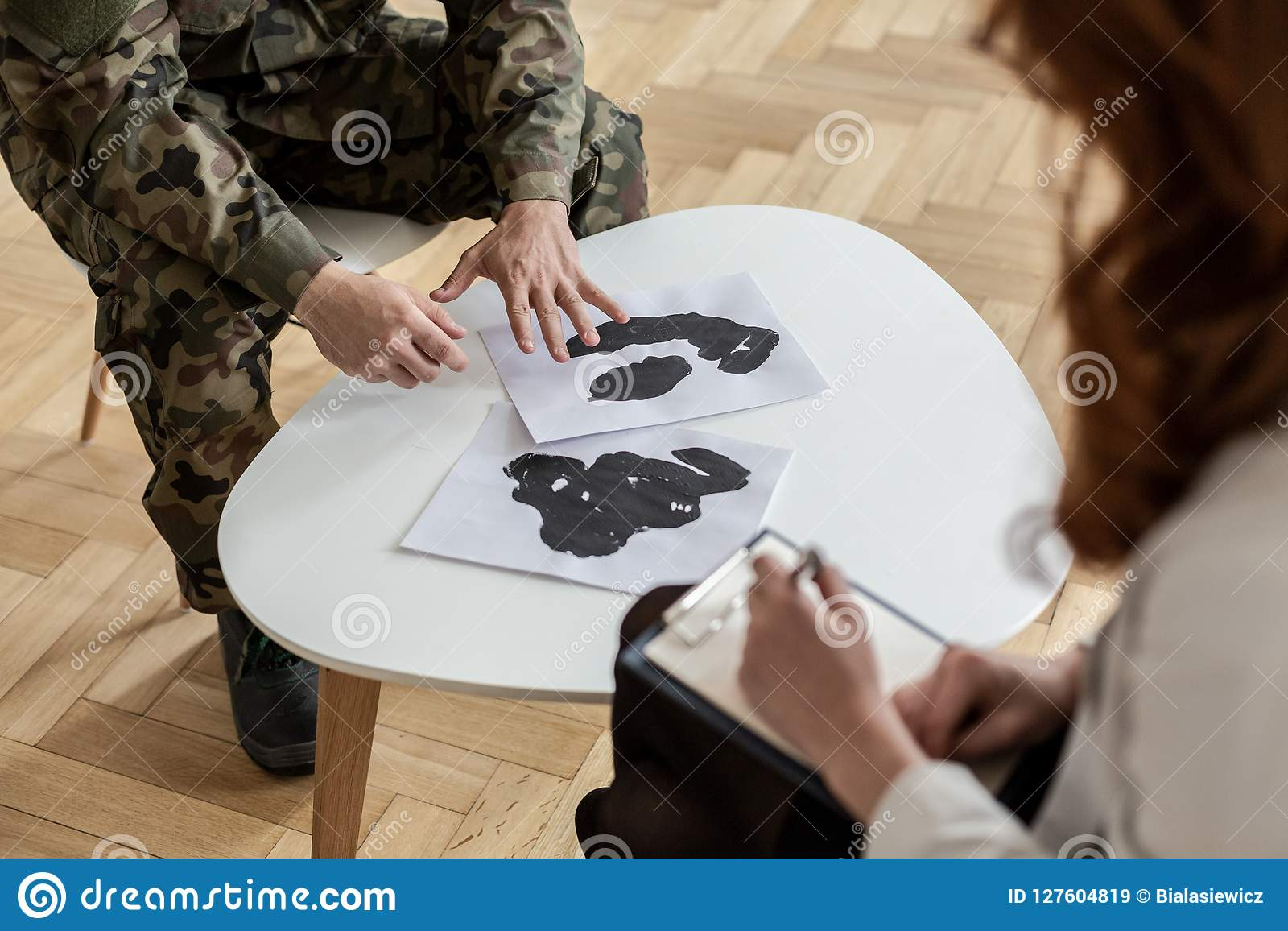 High angle on soldier in green uniform with posters during therapy with psychiatrist
