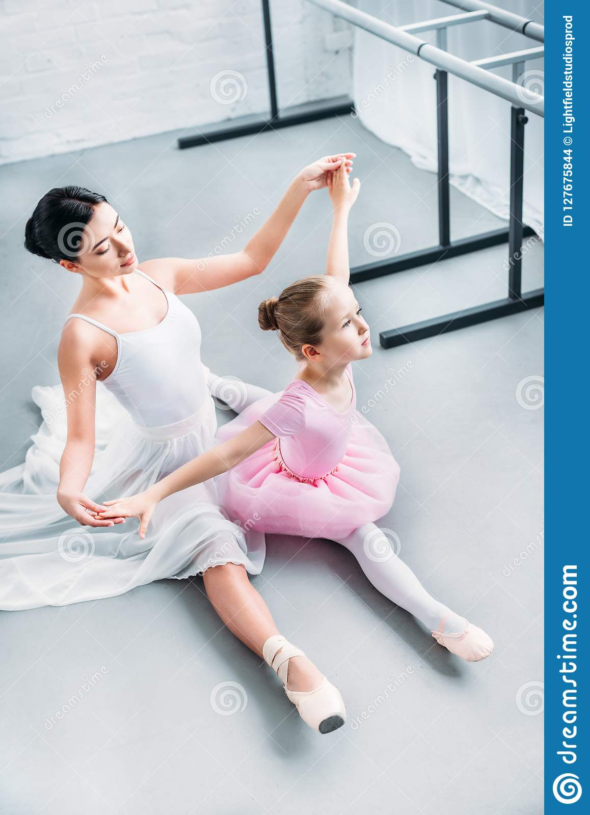 high angle view of adult ballerina exercising with cute little child