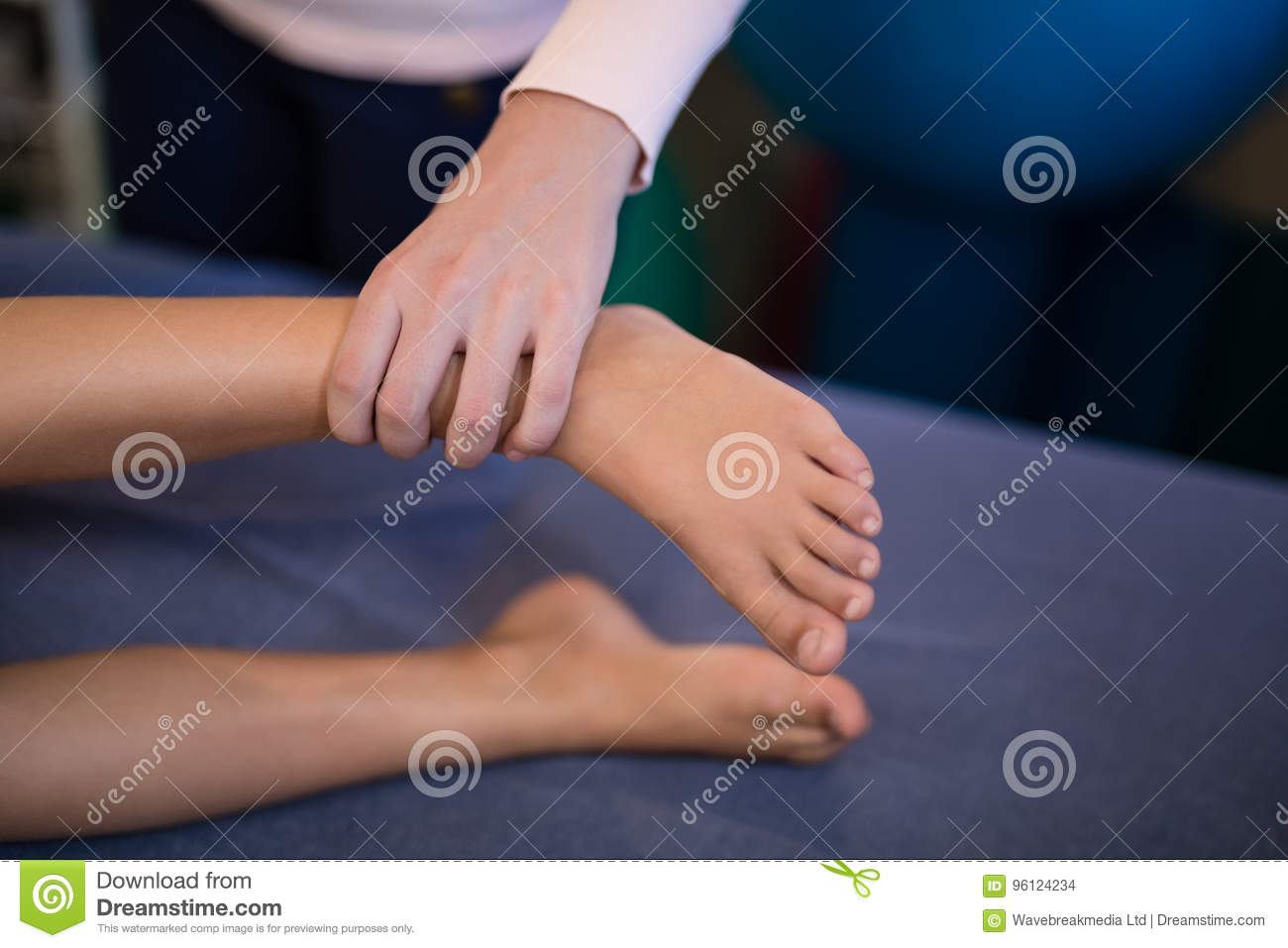 High angle view of female therapist examining feet with boy lying on bed