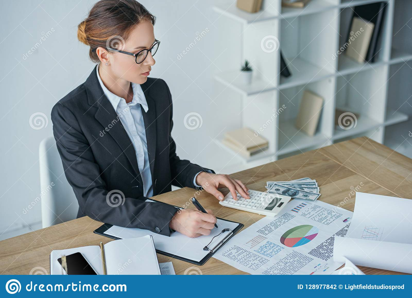 high angle view of financier working at table in office with calculator