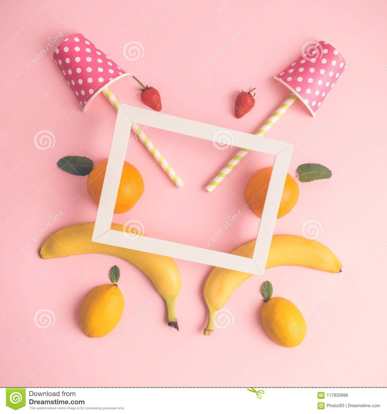 High angle view of fruits, paper cups with drinking straws and photo frame abstract.