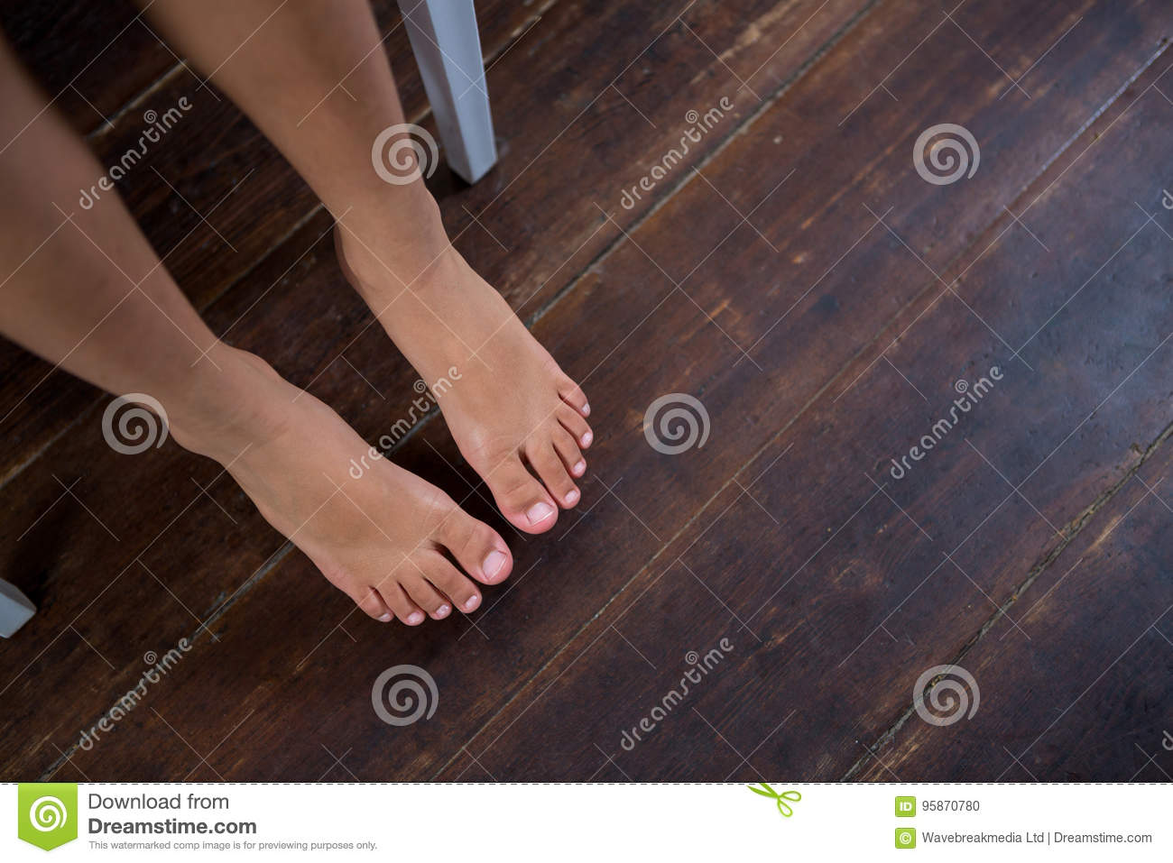 High angle view of girl sitting on chair over hardwood floor