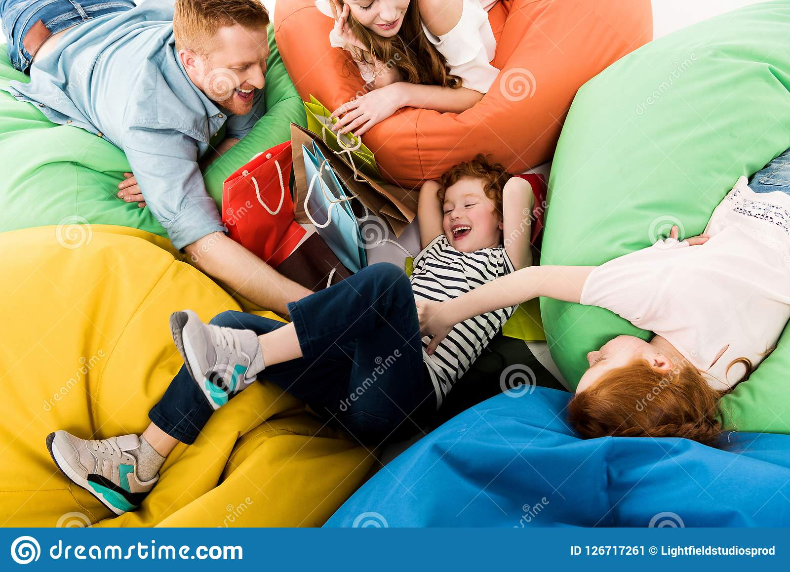 high angle view of happy family with shopping bags having fun on bean
