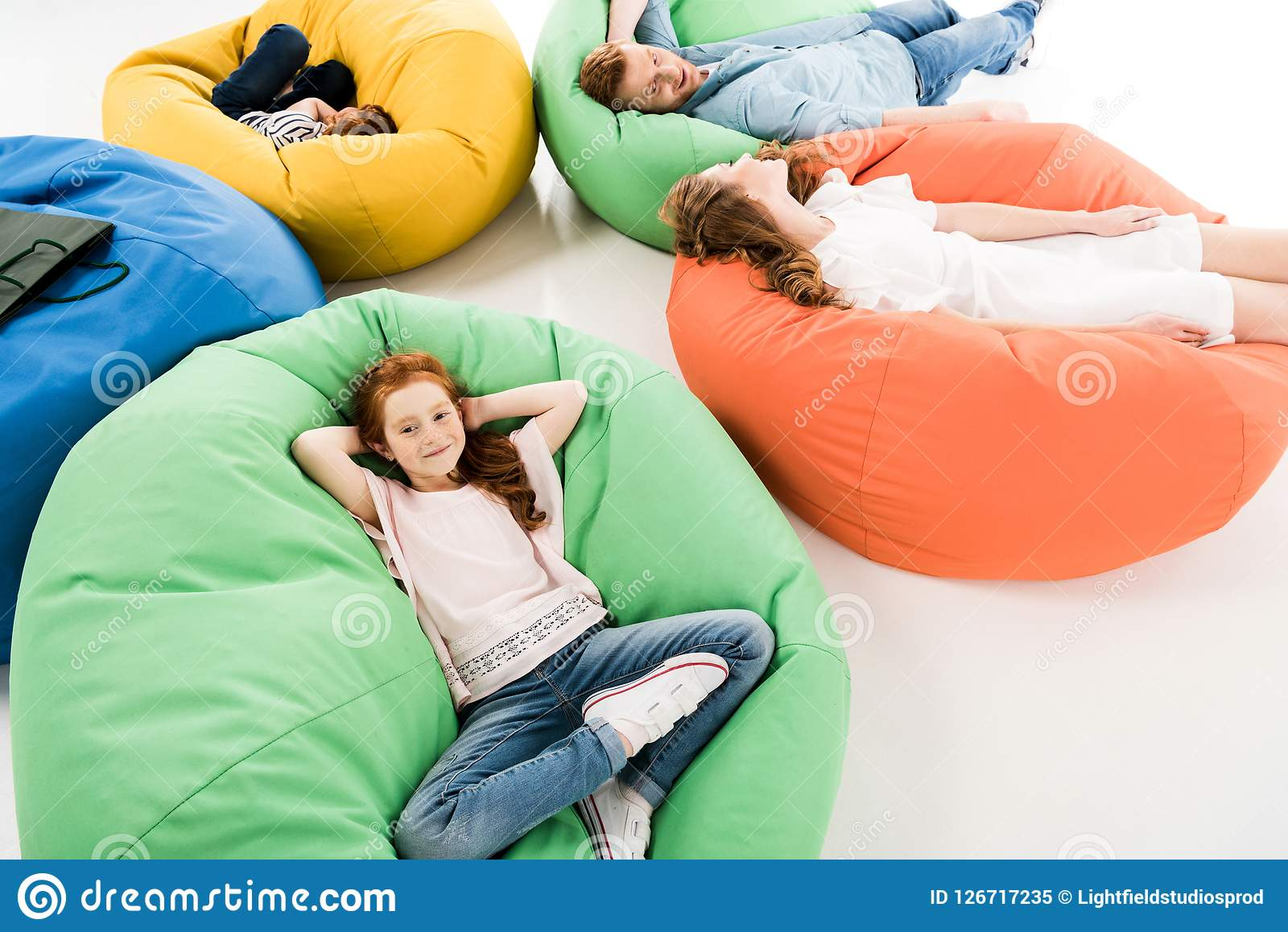 high angle view of happy family with two kids resting on bean bag chairs after shopping