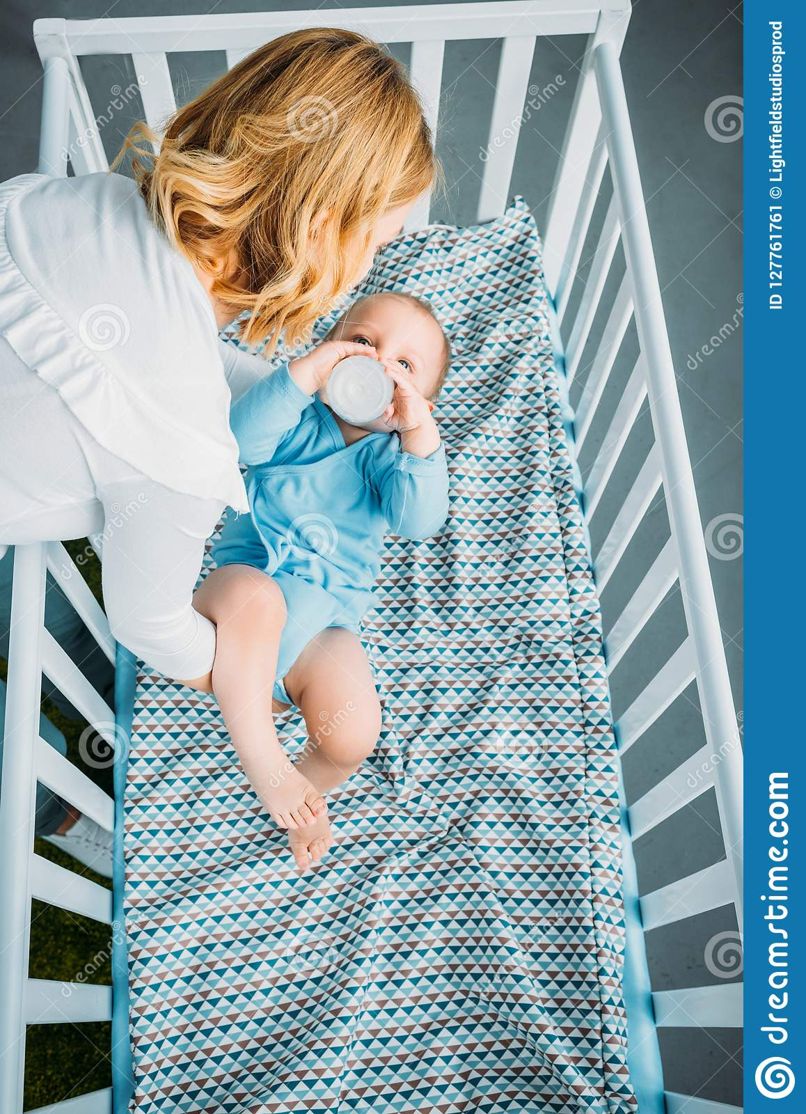 high angle view of mother putting her little child