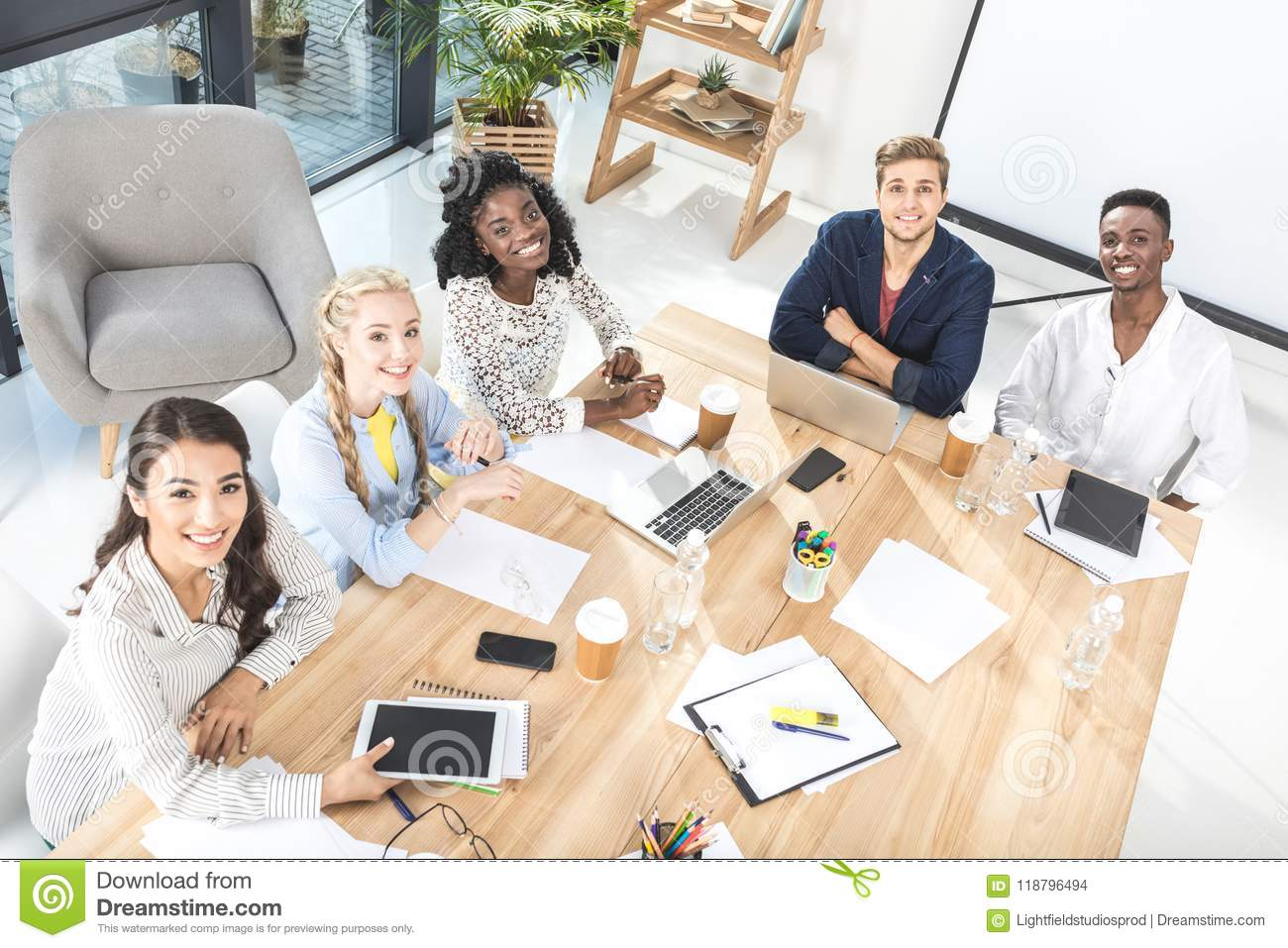 high angle view of multicultural group of business people looking at camera while sitting at table