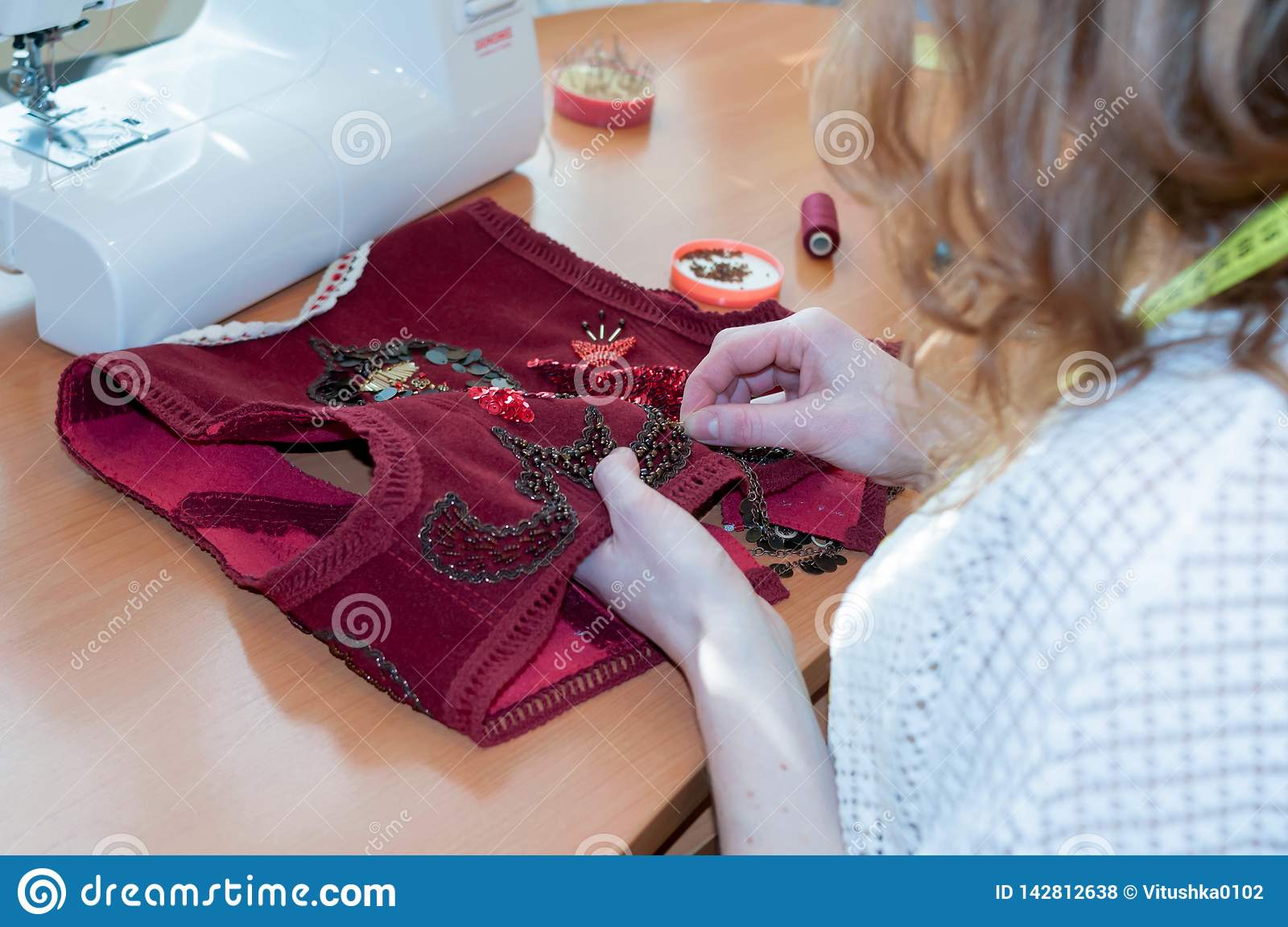 Seamstress sitting at table with sewing machine and embroiders red vest in studio
