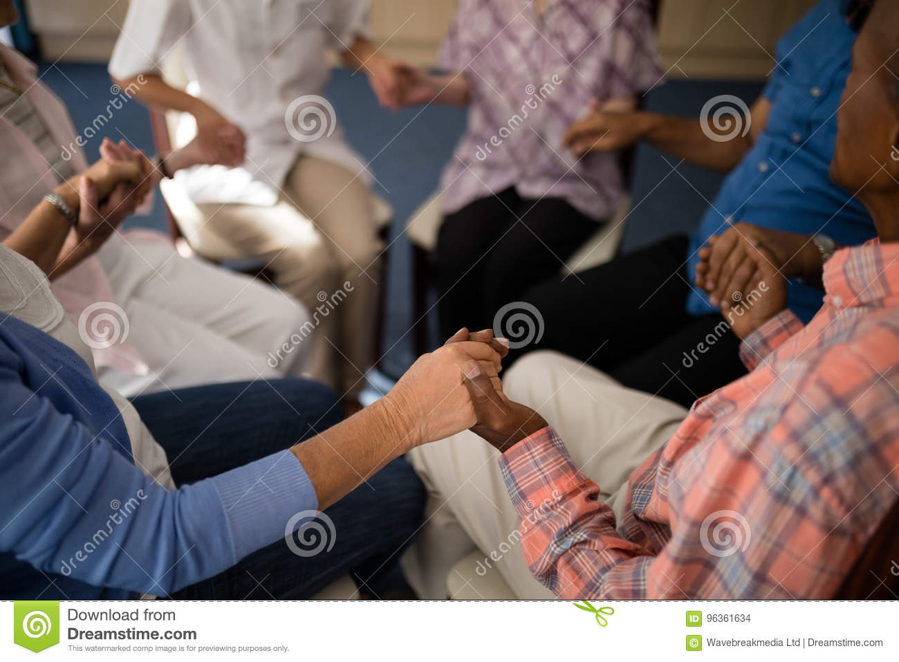 High angle view of seniors and female doctor holding hands while sitting on chairs