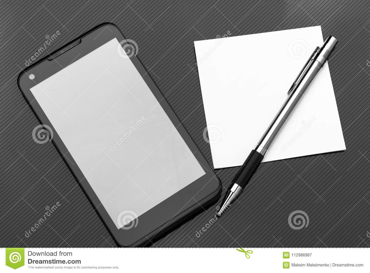 Smartphone with blank screen, pen and stickers on dark background.