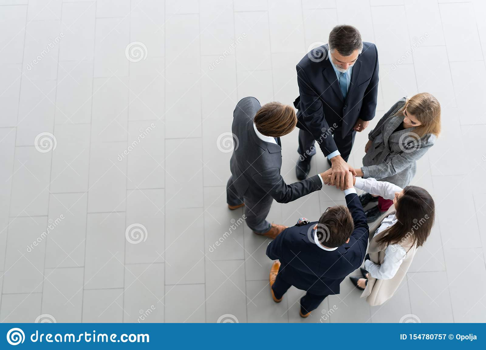 High angle view of a team of united coworkers standing with their hands together in a huddle in the modern office