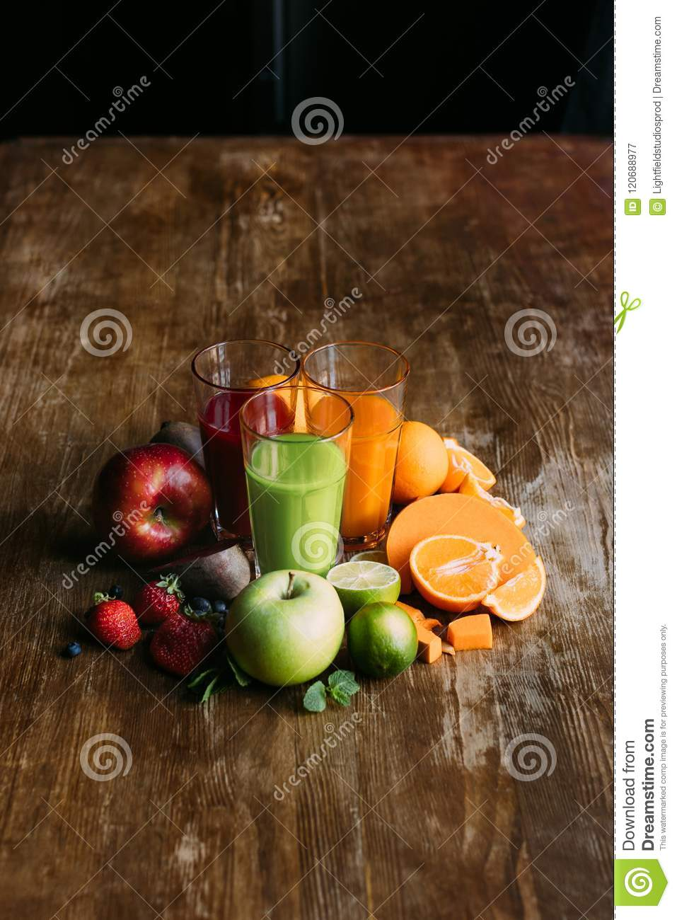 high angle view of various smoothies in glasses and fresh fruits with vegetables on wooden