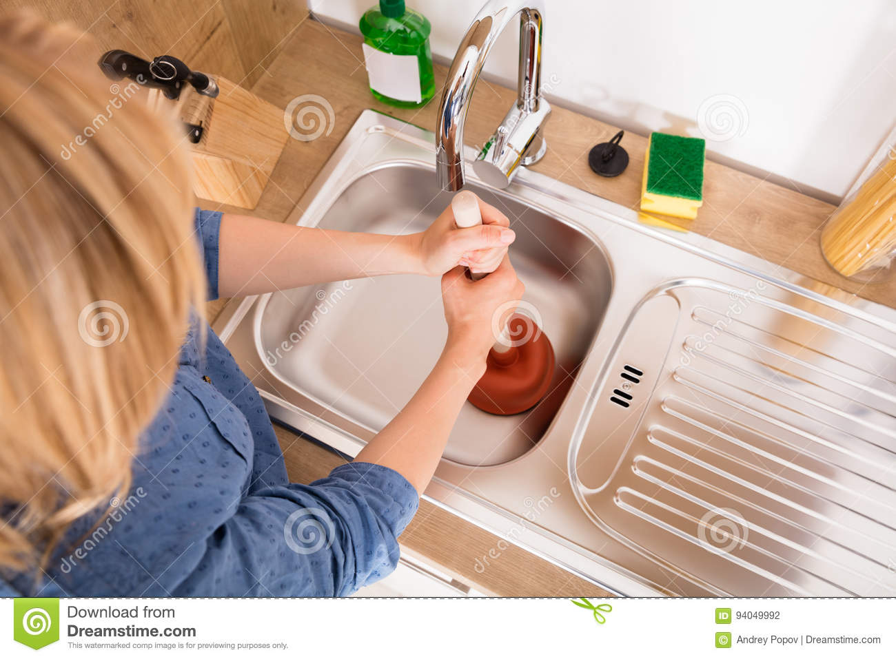 High Angle View Of Woman Using Plunger In Sink