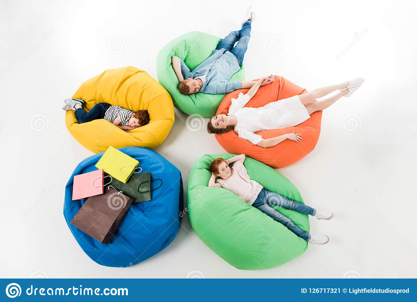 high angle view of young family with two kids resting on bean bag chairs after shopping