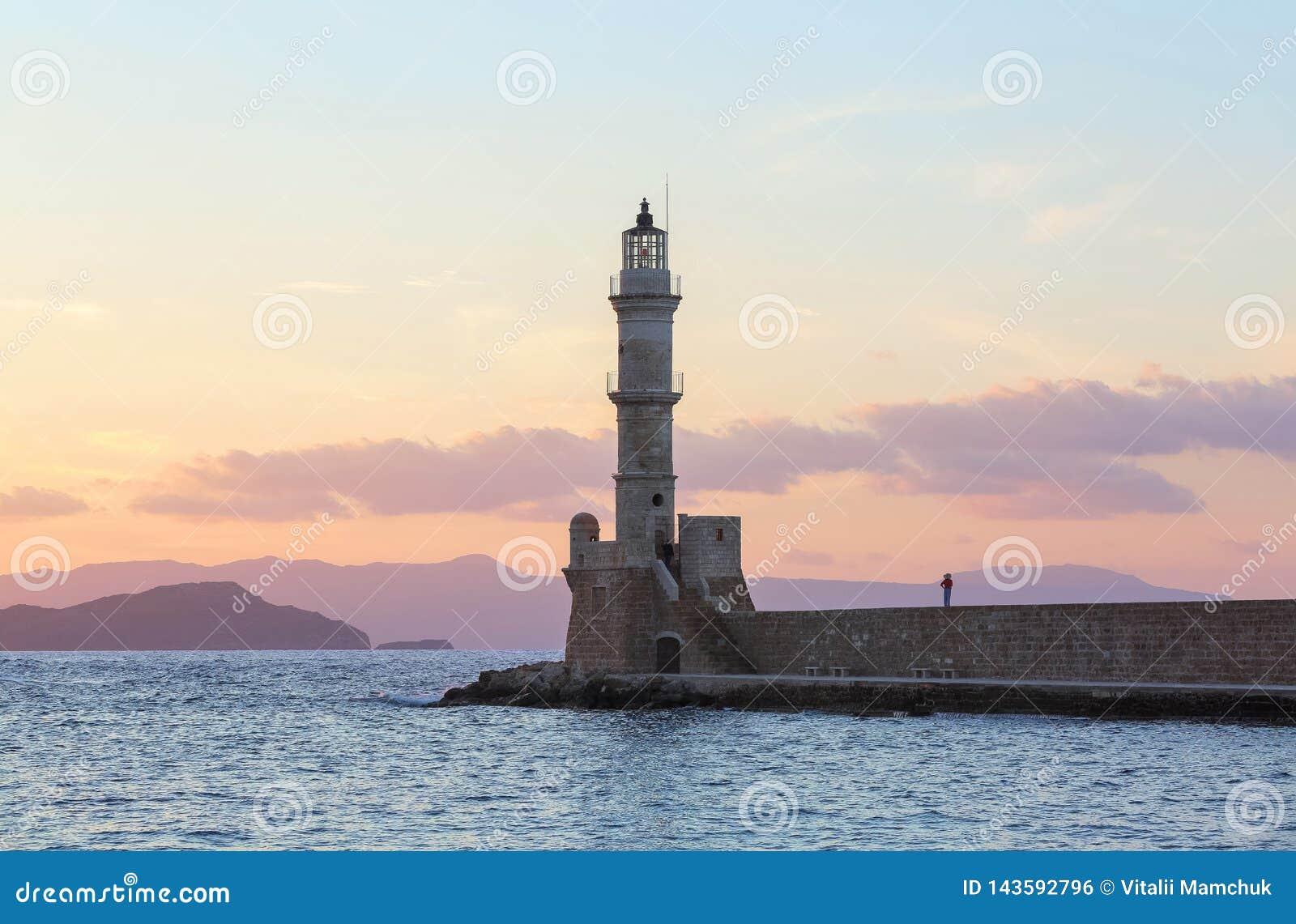 High, beautiful, ancient lighthouse made of bricks. Marvelous sunset lights the sky. Touristic resort Chania, Creete island.