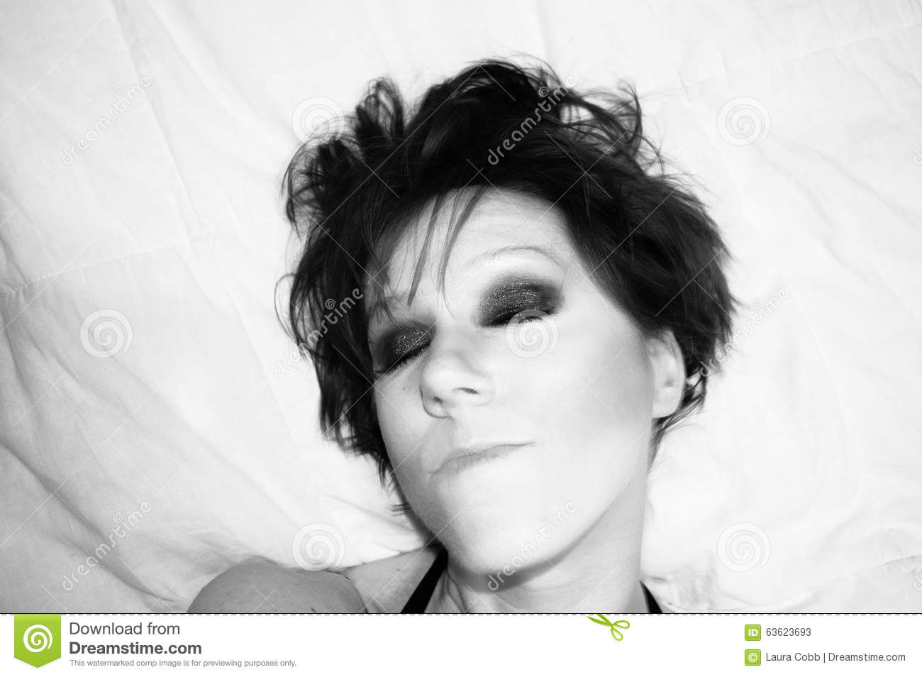A high contrast capture of the face of a woman in black and white with intense and dramatic eyes wearing dark eyeshadow