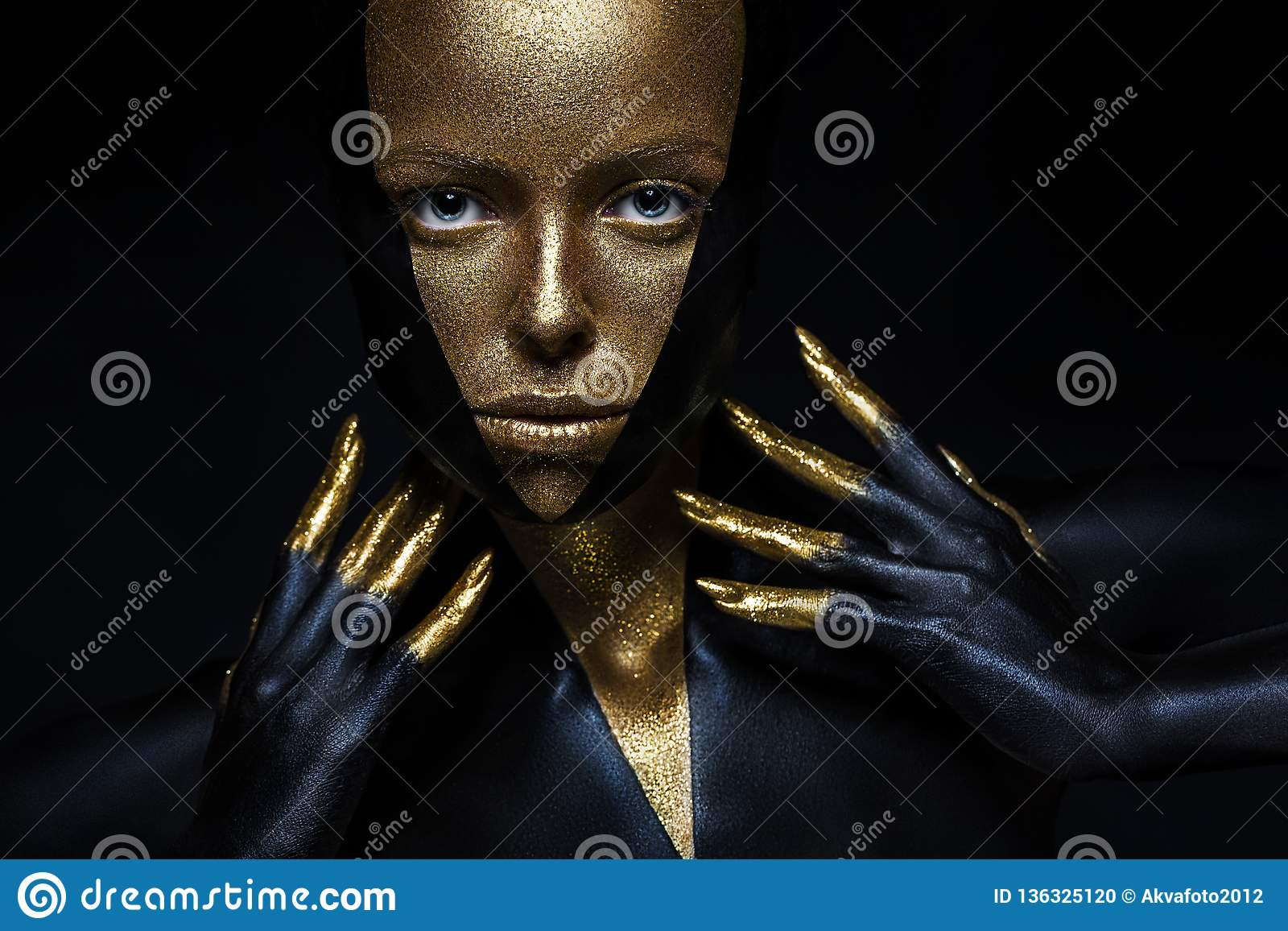 High fashion model with black and gold leather, golden fingers. Isolated on black background Beauty female face,