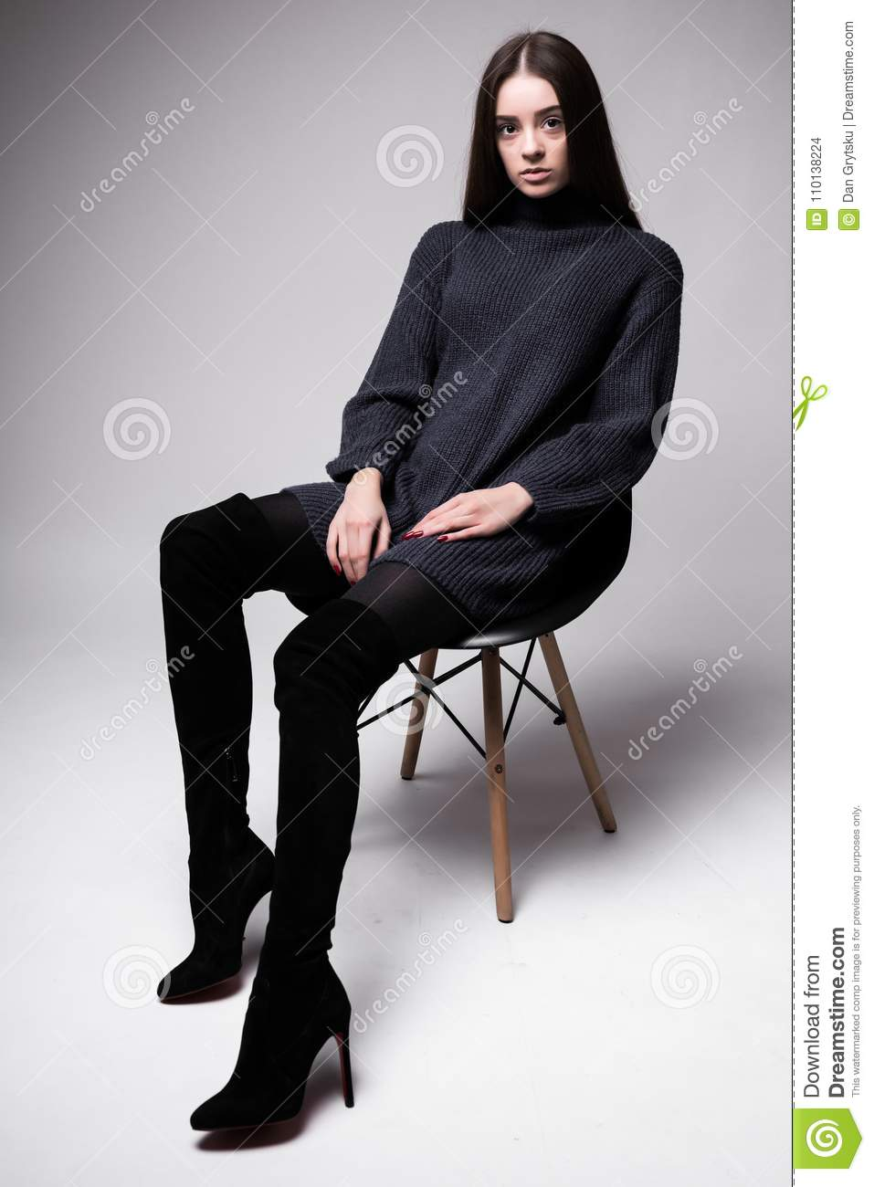 High fashion portrait of young elegant woman sittung on chair black clothes isolated on white background