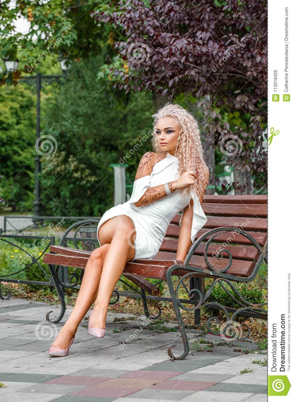 High fashion shot of young blond woman in white short dress