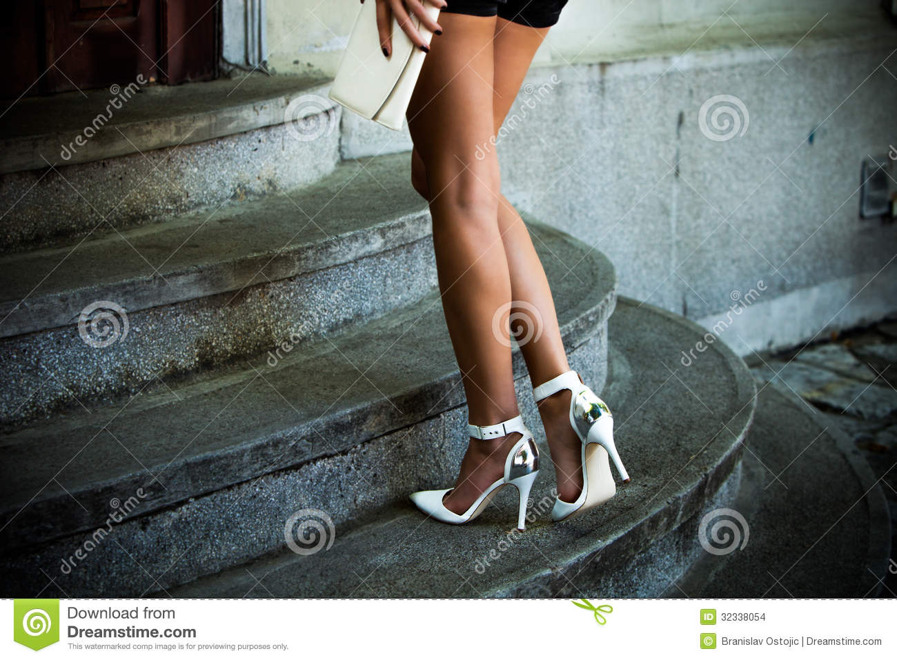 Woman legs on stairs in elegant white high heel shoes outdoor shot
