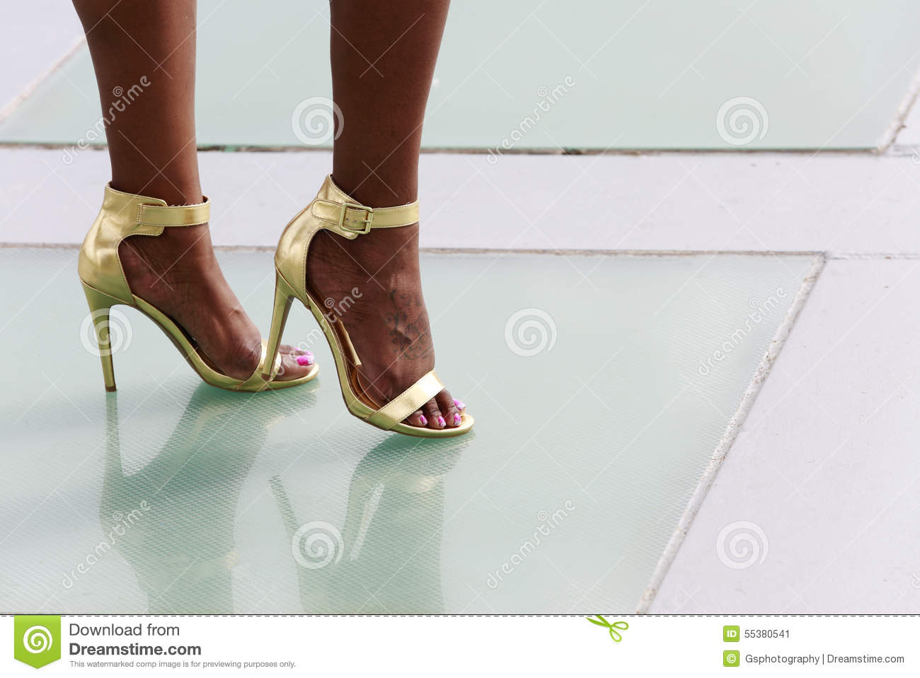 Legs of African-American woman in high heels shoes with tattoo.
