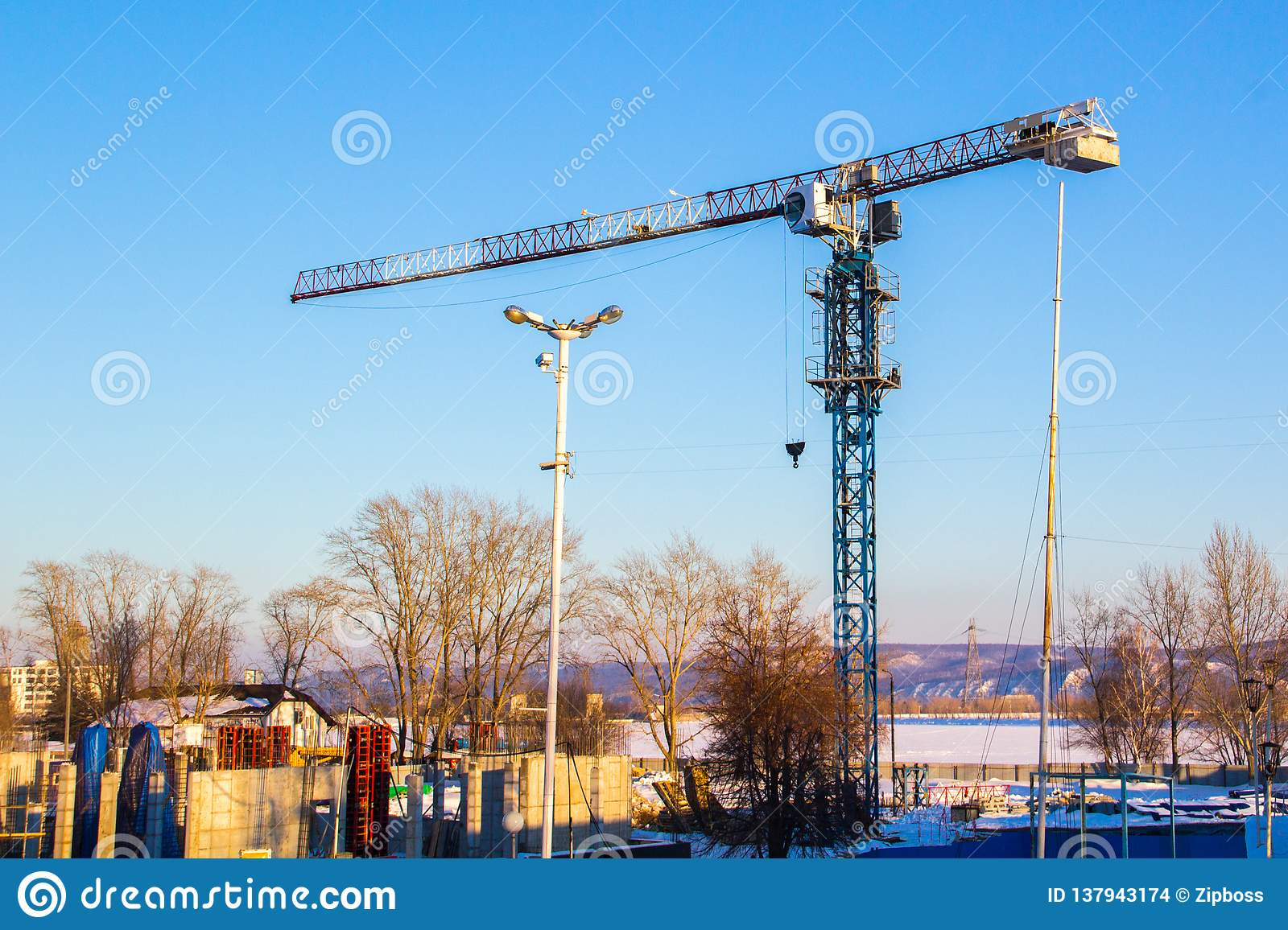 High lift construction crane with white, red and blue colors against a blue sky