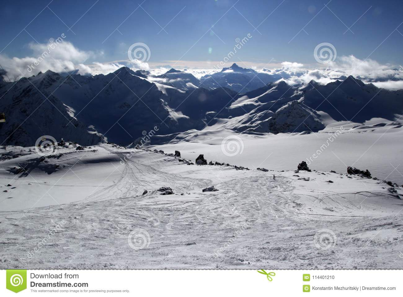 High mountains off-piste slopes for freeride with traces of skis and snowboards, sunny winter day, Caucasus Mountains, Elbrus